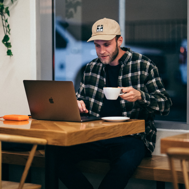 Man sitting at coffee shop looking at laptop