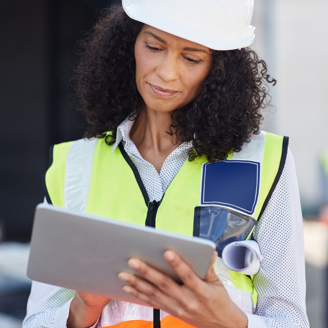 Woman in hardhat and vest working on a tablet