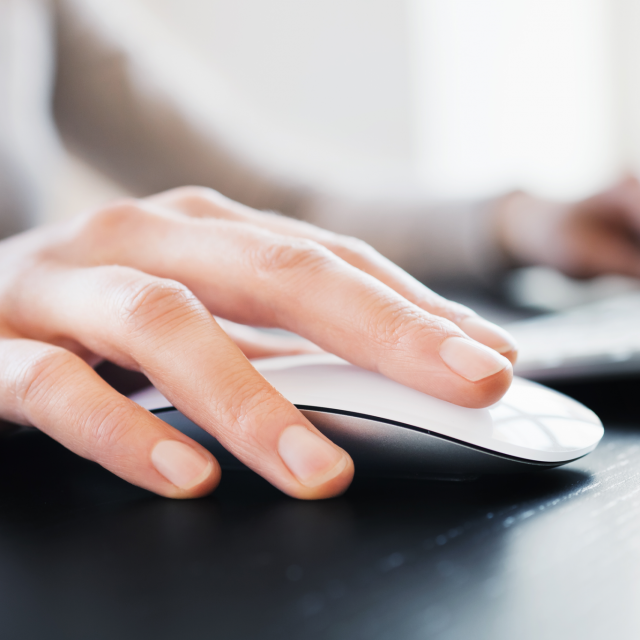 Closeup of a woman's hand on computer mouse
